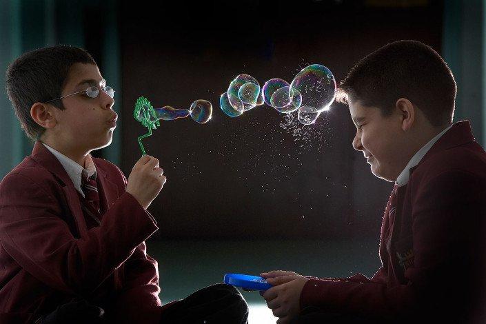 School pupil blows bubbles