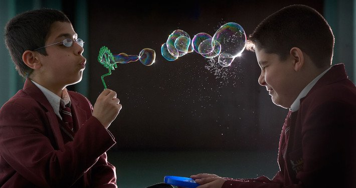 School pupil blows bubbles