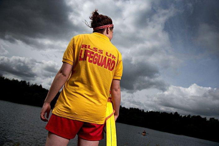 RLSS lifegaurd stands watch by a lake